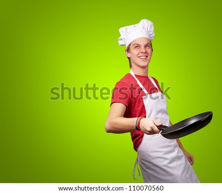Portrait Of A Chef Holding Pan On Green Background
