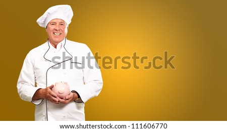 Portrait Of A Chef Holding Piggy Bank Isolated On Colored Background