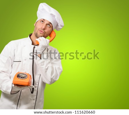 Portrait Of A Chef Talking On Phone On Green Background - stock photo