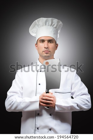 Portrait of a chef with a cleaver in his hands, gray background - stock photo