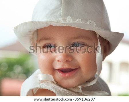 Portrait of a child a few months with white dress and hat on the day of her baptism.