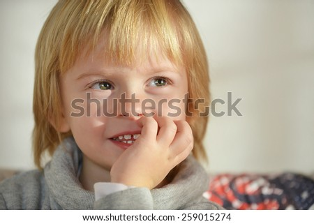 Portrait of a child aged three years old holding hand on his face - stock photo