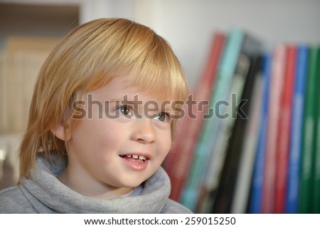 Portrait of a child aged three years old with books in the background