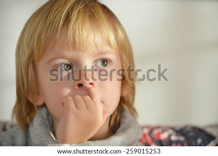 Portrait of a child aged three years old with fingers on his nose