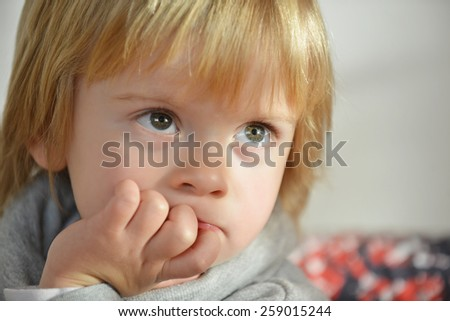 Portrait of a child aged three years old with hand on his chin - stock photo