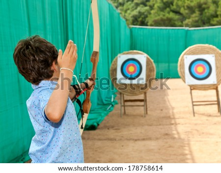 portrait of a child, archery, rear view - stock photo