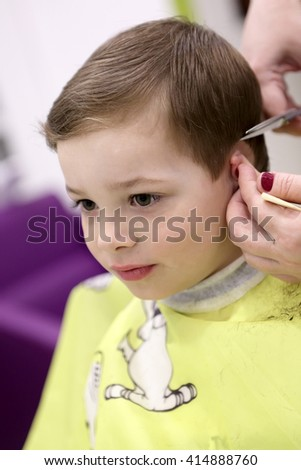 Portrait of a child at the barbershop - stock photo