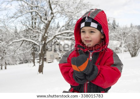 Portrait of a child boy clapping his hands in gloves or mittens in winter in snow.
