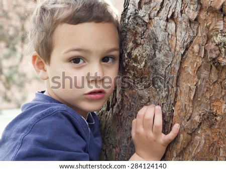 Portrait of a child boy holding and hugging tree trunk. - stock photo