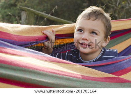 Portrait of a child boy in colorful hammock in a garden.  - stock photo