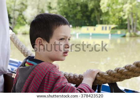 Portrait of a child boy on a river boat or barge looking at distance.  - stock photo