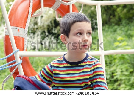 Portrait of a child boy  on a river boat with safety ring lifebuoy, nature in a background. - stock photo