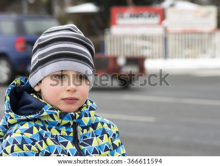 Portrait of a child boy standing by busy road in winter time, road safety concept.