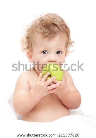portrait of a child curly hair eats a green apple on white background
