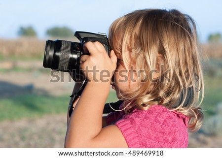 Portrait of a child holding a photo camera