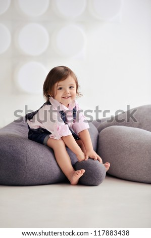 Portrait of a child in the studio. Girl sitting on cushions. Beautiful child portrait. - stock photo
