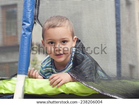 Portrait of a child peeking from a trampoline through the door in safety net. - stock photo