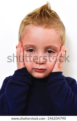portrait of a child playfully clutching his face with his hands