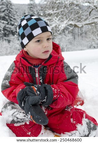 Portrait of a child sitting in fresh snow in winter  garden. - stock photo