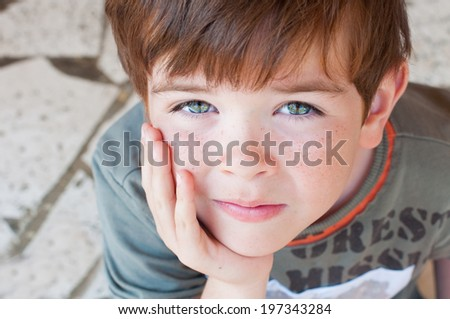Portrait of a child with his hand at his face - stock photo