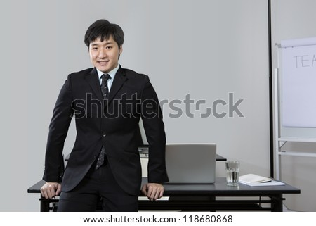 Portrait of a Chinese business man leaning on his desk - stock photo
