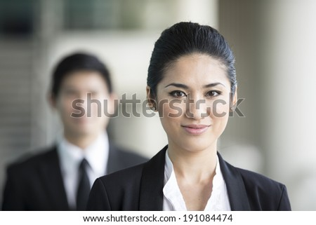 Portrait of a Chinese business woman with a happy expression. Colleague is out focus. - stock photo