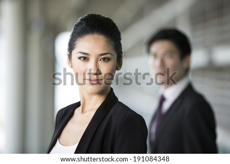 Portrait of a Chinese business woman with a serious expression. Colleague is out focus. - stock photo