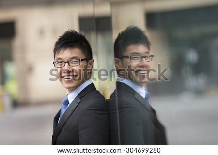 Portrait of a Chinese businessman outside modern office building. Asian businessman smiling & looking at the camera. - stock photo