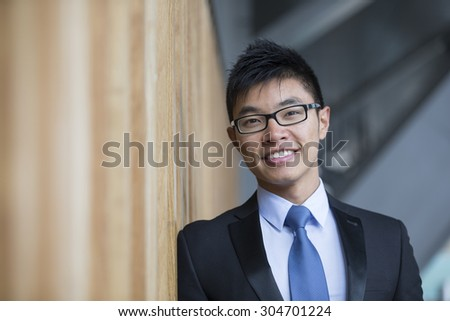 Portrait of a Chinese businessman outside modern office building. Asian businessman smiling & looking at the camera with blurred office buildings as a background. - stock photo