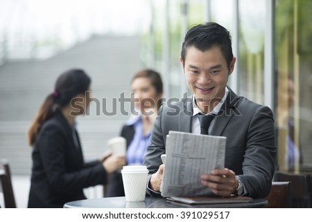 Portrait of a Chinese businessman reading a newspaper and using his smart phone in a cafe.