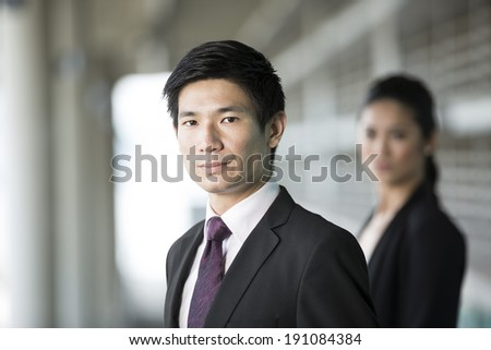 Portrait of a Chinese businessman with a serious expression. Colleague is out focus. - stock photo
