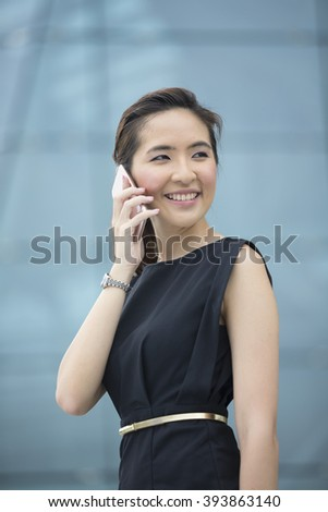 Portrait of a Chinese businesswoman standing outside talking on her smart phone. - stock photo