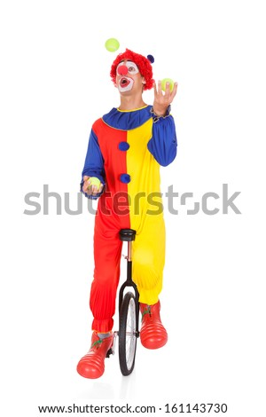 Portrait Of A Clown Juggling With Balls On Unicycle Over White Background - stock photo