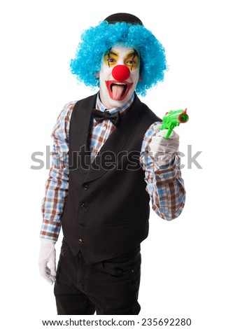 portrait of a clown with a gun toy - stock photo
