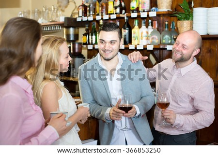 Portrait of a company of friends in a bar two men and two women are having a good time drinking coffee and wine - stock photo