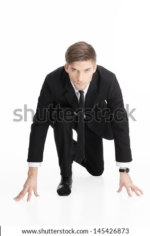 Portrait of a competitive businessman at starting position. Vertical shot. Isolated on white.