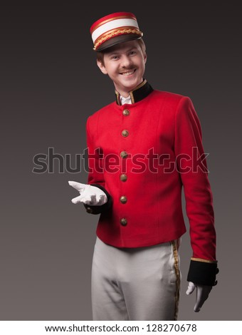 Portrait of a concierge (porter) in a red jacket on a gray background. - stock photo