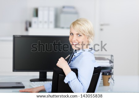 Portrait of a confident and beautiful young businesswoman smiling at office desk - stock photo