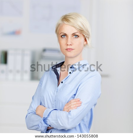 Portrait of a confident and beautiful young businesswoman standing with arms crossed - stock photo