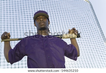 Portrait of a confident baseball player holding bat during practice against the net - stock photo