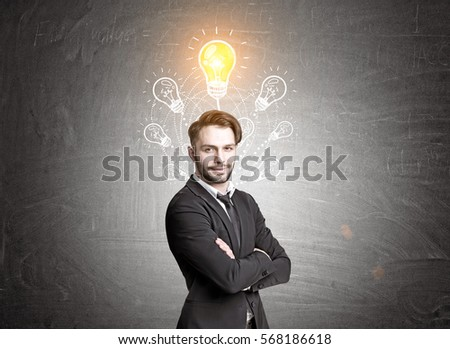 Portrait of a confident bearded businessman standing with crossed arms near a blackboard with seven light bulb sketches. One of them is shining.