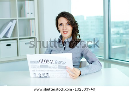 Portrait of a confident business lady reading a fresh newspaper - stock photo