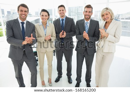 Portrait of a confident business team clapping hands together in a bright office - stock photo