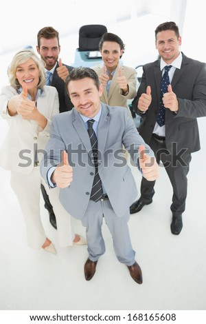 Portrait of a confident business team gesturing thumbs up in a bright office