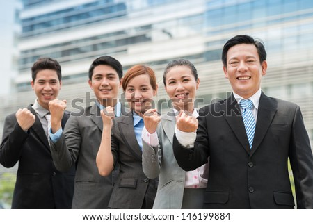 Portrait of a confident business team showing fist at camera - stock photo