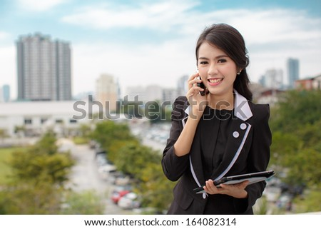 Portrait of a confident business woman talking on phone and hold tablet  - stock photo