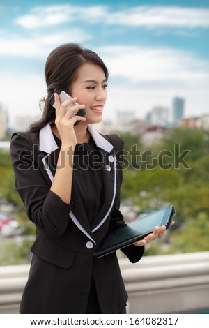 Portrait of a confident business woman talking on phone and hold tablet