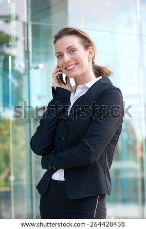 Portrait of a confident business woman walking and talking on mobile phone - stock photo