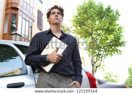 Portrait of a confident businessman leaning on a car in the city and holding his laptop while looking ahead.