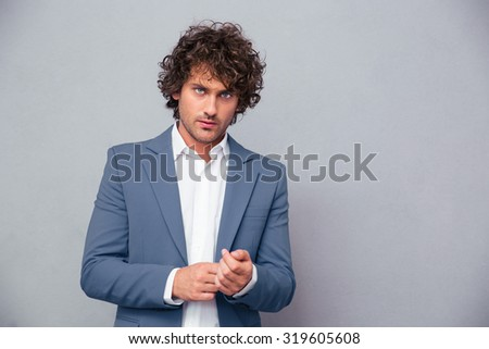 Portrait of a confident businessman looking at camera over gray background - stock photo